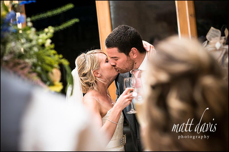 Couple kiss during wedding speeches at Kingscote Barn in the Cotswolds