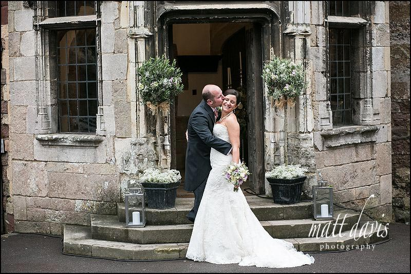 Bride and groom kiss in the main doorway at Berkeley Castle