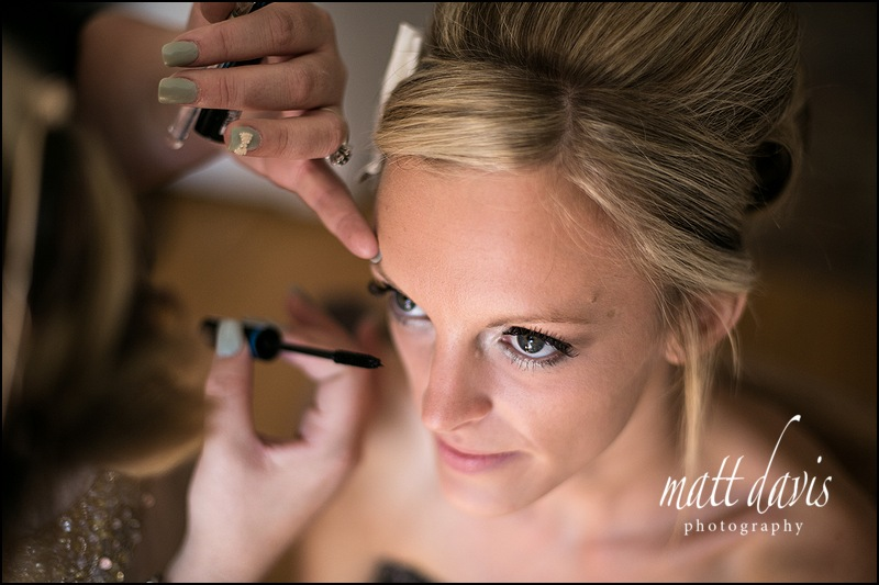 Stunning wedding photography of bridal preps showing bride eyes having mascara applied.
