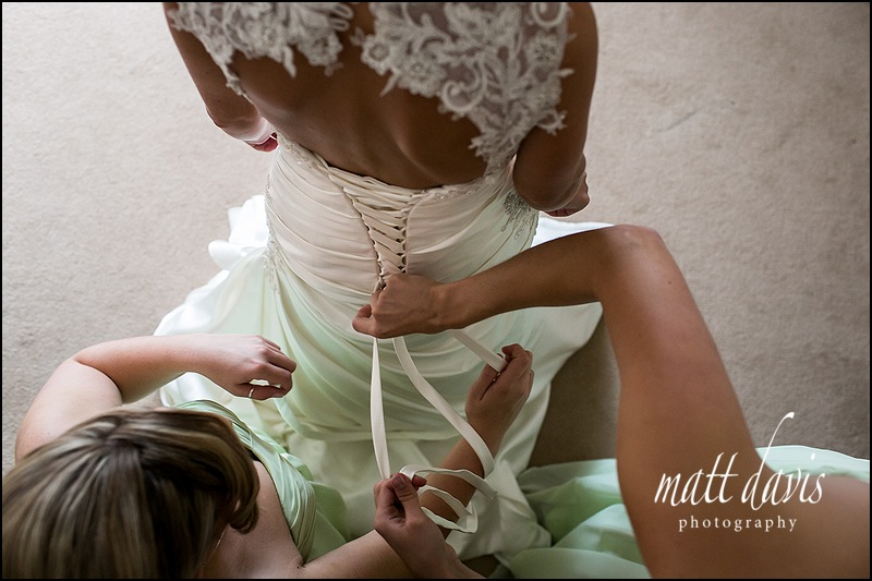Bride having wedding dress tied by bridesmaids in sage green dresses