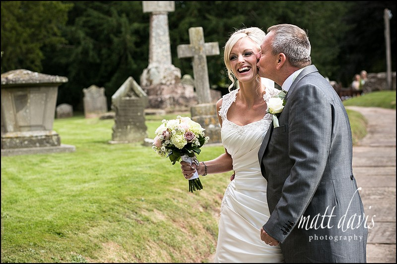 Father kissing the bride prior to getting married at St John The Baptist, Kings Caple, Herefordshire.