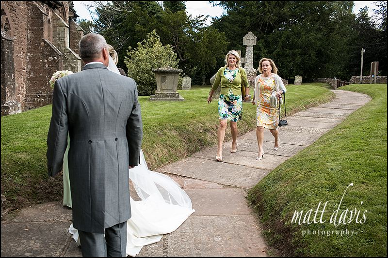 Photojournalism at a wedding capturing the wedding guests late arrival at St John The Baptist, Kings Caple, Herefordshire.
