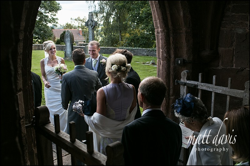 Guests leaving a church near Caradoc Court being greeted by married couple.