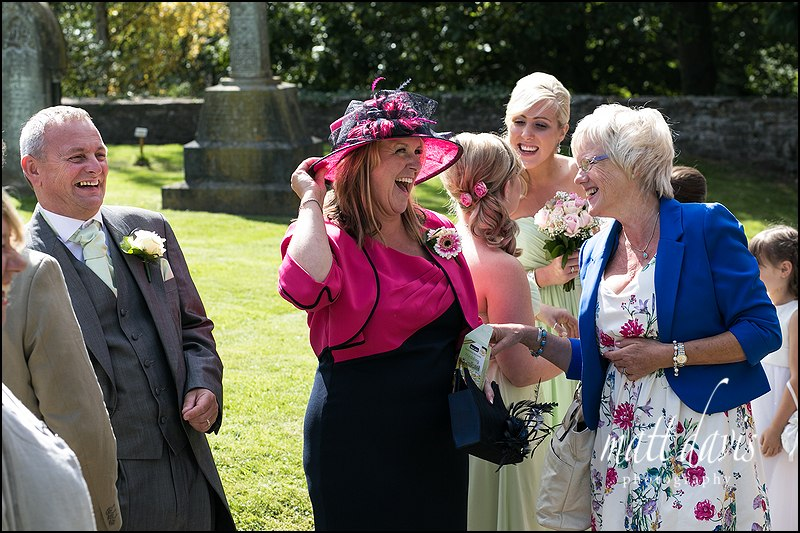 Wedding guests laughing in the sunshine