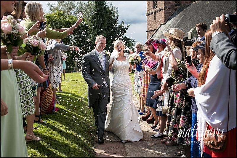 Caradoc Court wedding photos with couple having confetti thrown leaving the church
