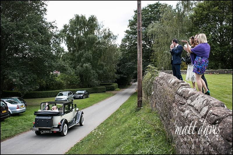 Wedding couple leaving church and waving to guests as they depart to Caradoc Court