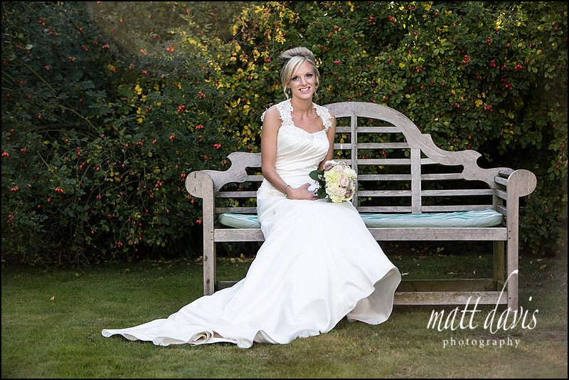 classic stylish wedding photography at Caradoc Court of bride on a bench