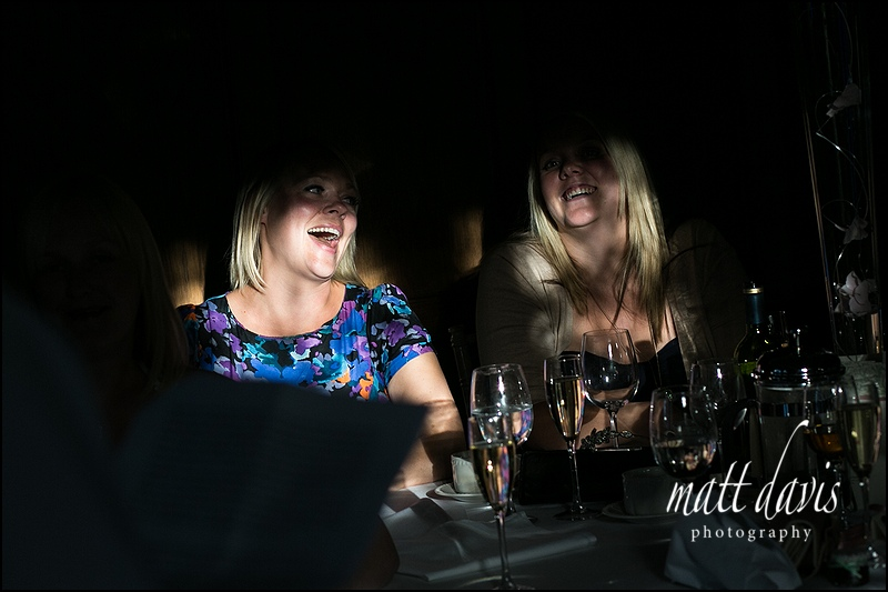 Natural light photography at Caradoc Court with guests laughing during wedding speeches
