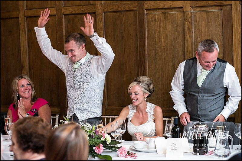 Groom with hands in the air doing a wedding speech at Caradoc Court