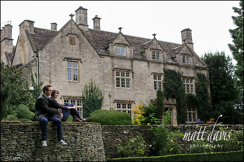 Engagement photos at Barnsley House of couple sat on wall outside