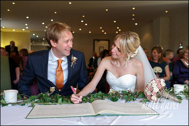 wedding couple sign the register during a civil ceremony at The Bear of Rodborough in Gloucestershire