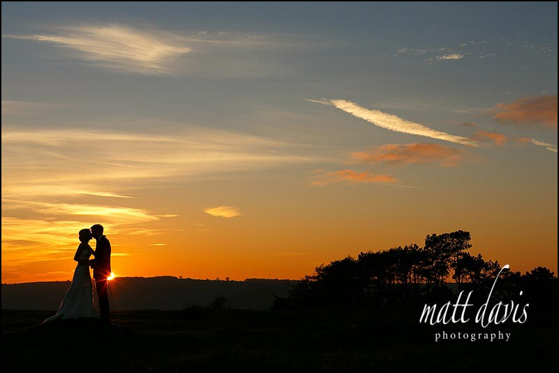 stunning wedding photo taken at sunset of couple on Rodborough Common