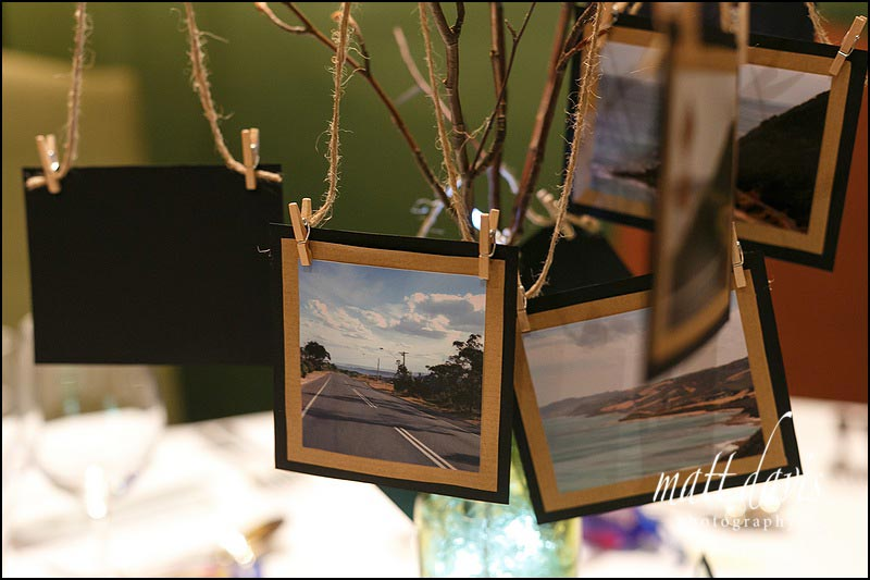 Wedding details - photos hung from twigs at the table centre