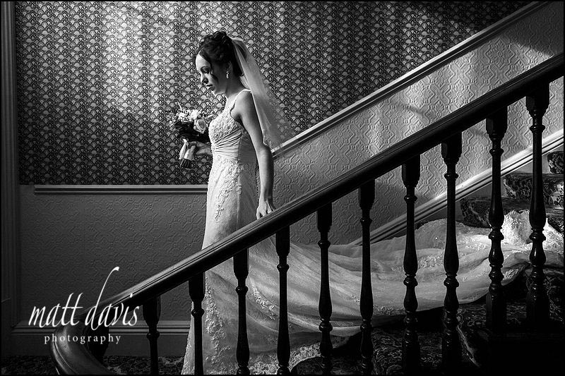 Wedding photography at Limpley Stoke Hotel with bride walking down the staircase