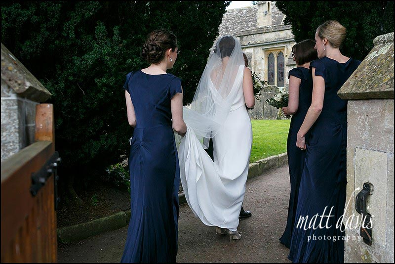 Bride wearing a backless wedding dress with bridesmaids holding the veil