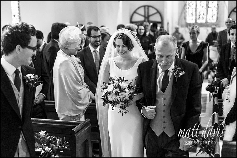 Bride walks down the aisle during her wedding at  St Mary's church Barnsley, Gloucestershire