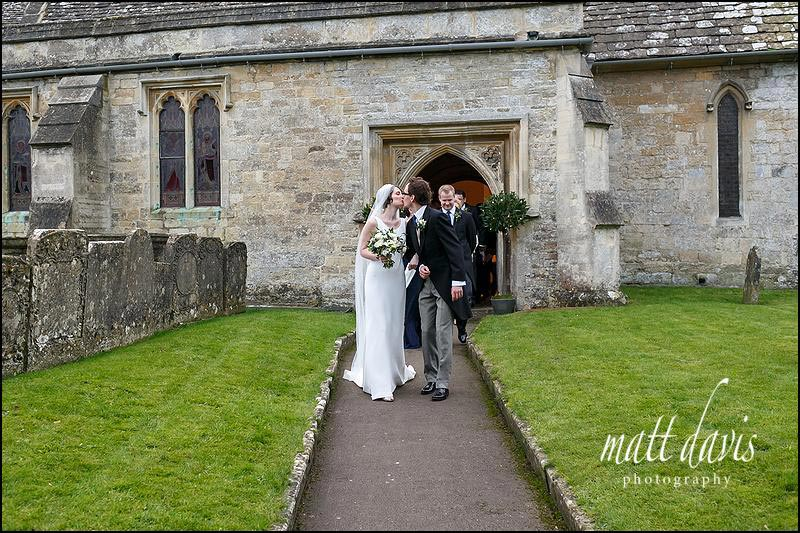 Couple kiss outside St. Mary's church in Barnsley, Gloucestershire