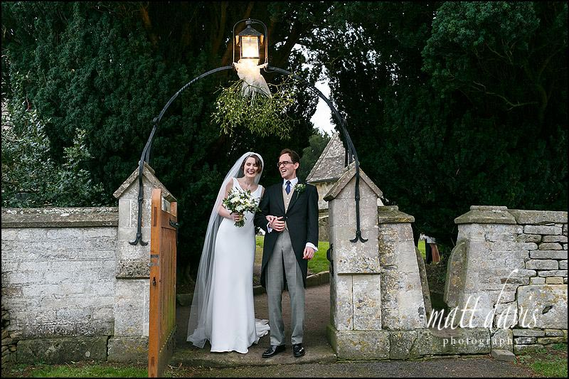 Wedding couple stand by the gate of St. Mary's church in Barnsley, Gloucestershire