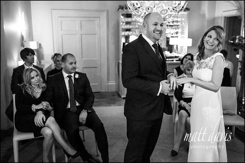 Bride and groom smiling during ring exchange at a small wedding at Barnsley House