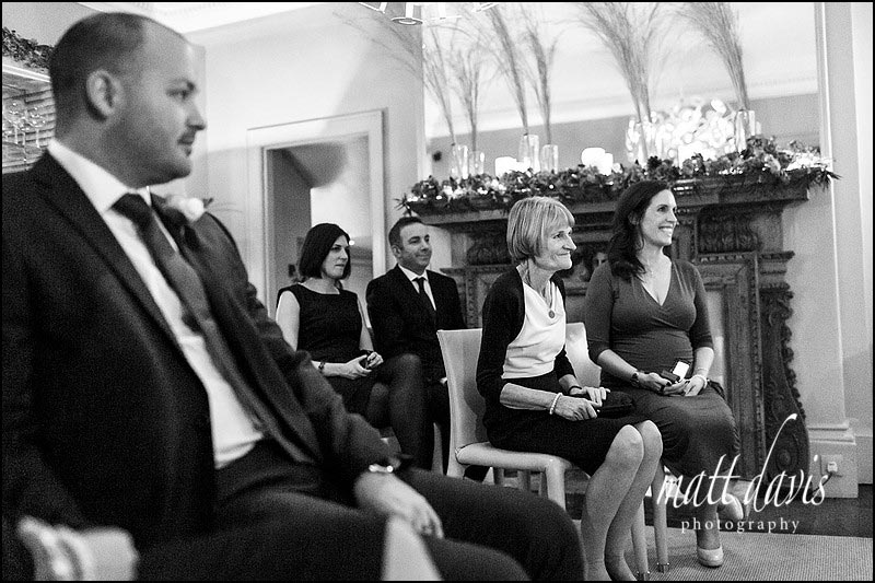wedding guests smiling watching an intimate winter wedding at Barnsley House