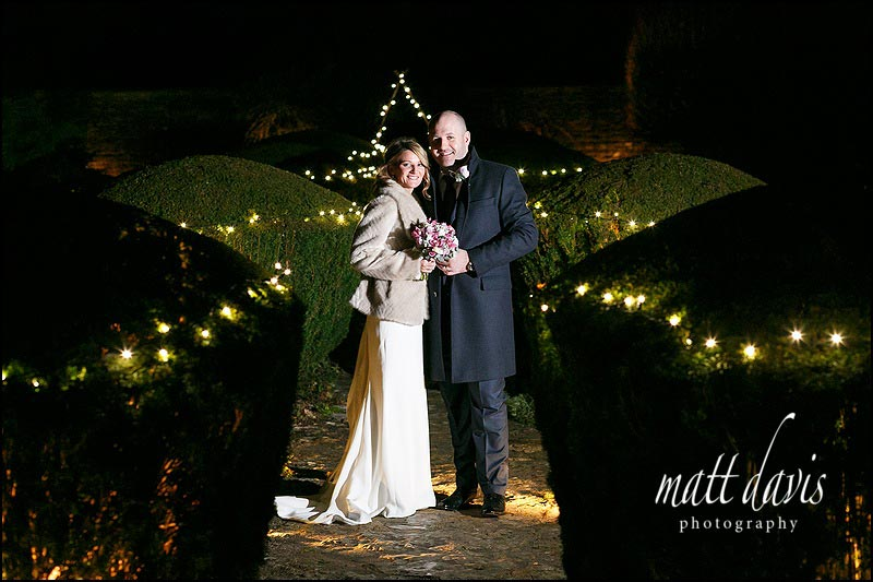 Couple pose for a winter wedding photo at their small wedding at Barnsley House
