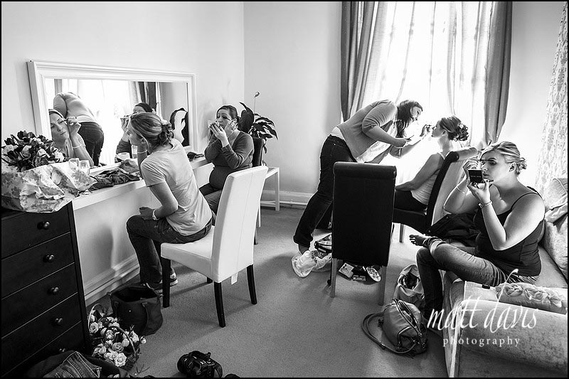 Bridesmaids applying make-up in the bridal suite at Eastington Park, Gloucestershire