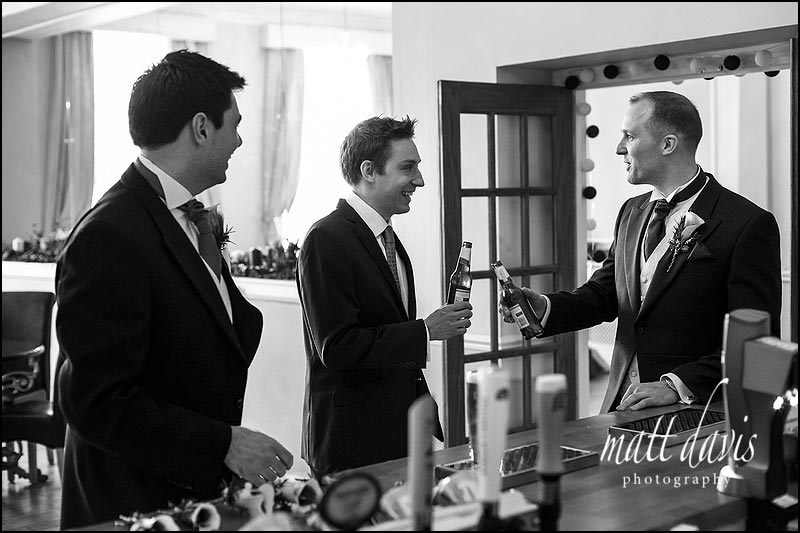 Groom and ushers drink in the bar at Eastington Park prior to the wedding ceremony