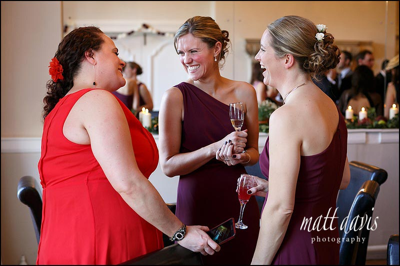 Bridesmaids talk to guests at a wedding at Eastington Park in Gloucestershire