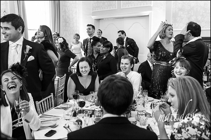 Wedding guests laughing during a wedding quiz at Eastington Park