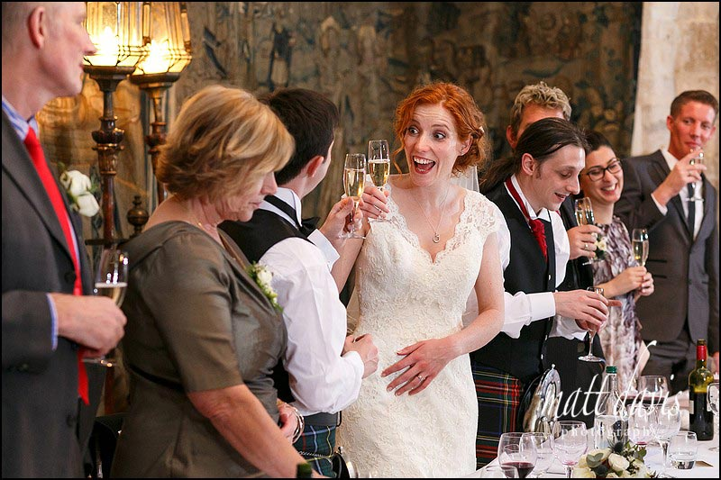 bride toasts the groom during speeches at Berkeley Castle, Gloucestershire