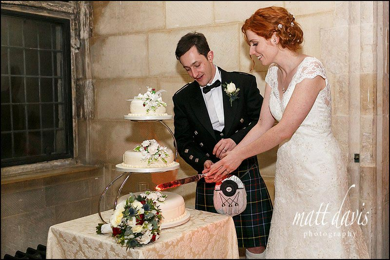 bride and groom cutting the wedding cake at a winter wedding at Berkeley Castle