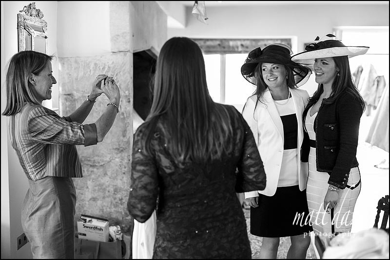 Mother of the bride photographs guests in wedding hats