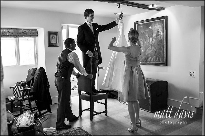 Wedding dress being lifted down from a hook to be carried to the brides bedroom