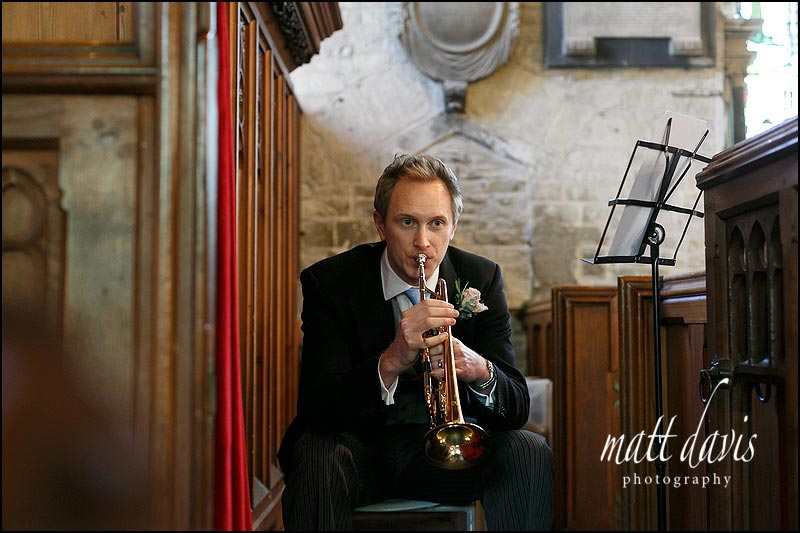 Trumpet player at a wedding at Holy Trinity church, Cold Ashton, Gloucestershire