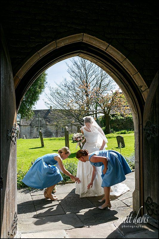 Bride in the doorway before a wedding at Holy Trinity church, Cold Ashton, Gloucestershire