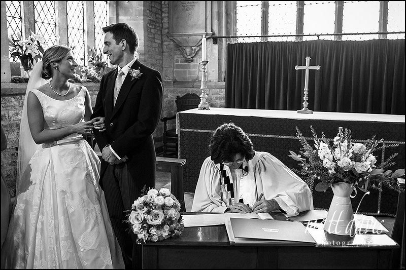 Black and white documentary wedding photography of vicar signing the wedding register
