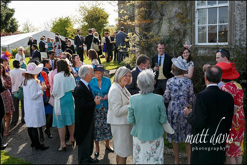 Wedding guests enjoying a drinks reception on the lawn outside the Marquee at Hamswell House
