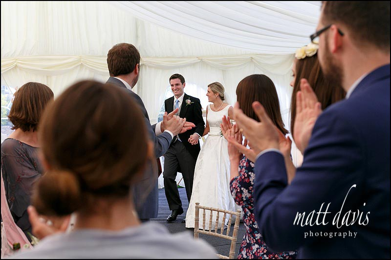 Bride and groom enter the Marquee at Hamswell House wedding