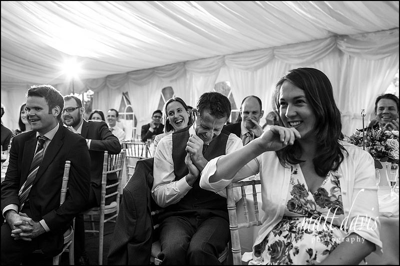 Guest reactions to wedding speeches in the Marquee at a Hamswell House wedding