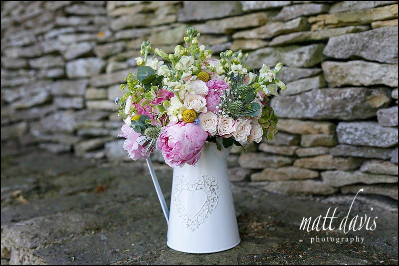 Mixed spring flowers in country style wedding bouquet presented in a vintage jug