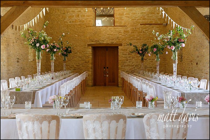 Tall vases of flower arrangements used at Kingscote Barn to decorate the wedding reception