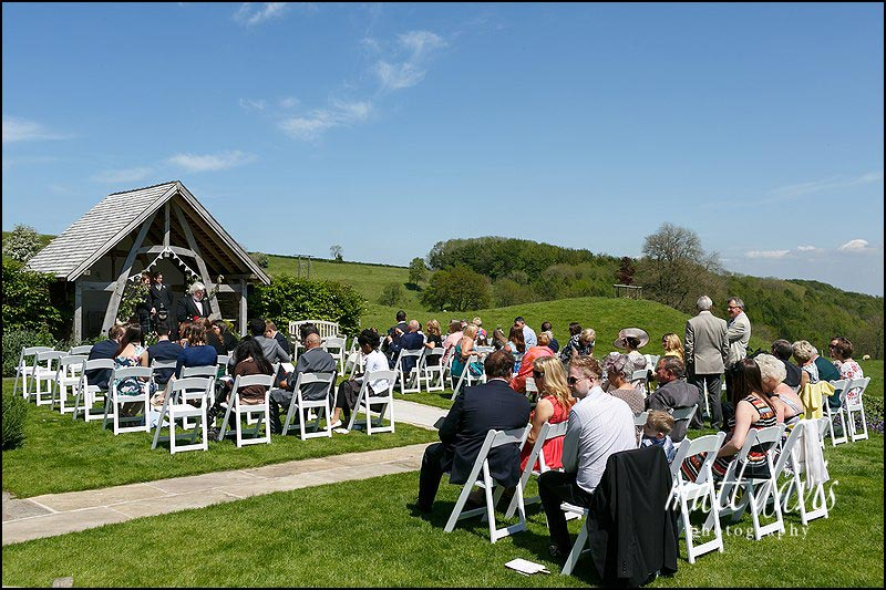 An outdoor wedding ceremony at Kingscote Barn