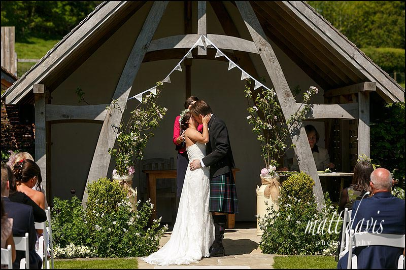 Couple kiss during an outdoor wedding at Kingscote Barn