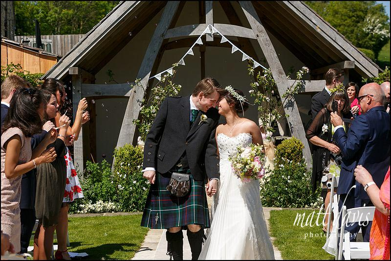 Couple kiss as they walk down the aisle during an outdoor wedding at Kingscote Barn