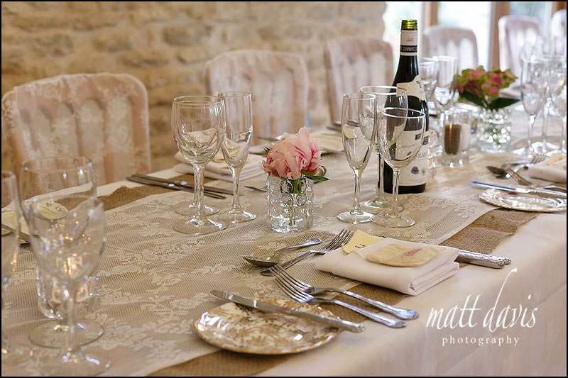 Table settings with silk and hessian table runners at Kingscote Barn