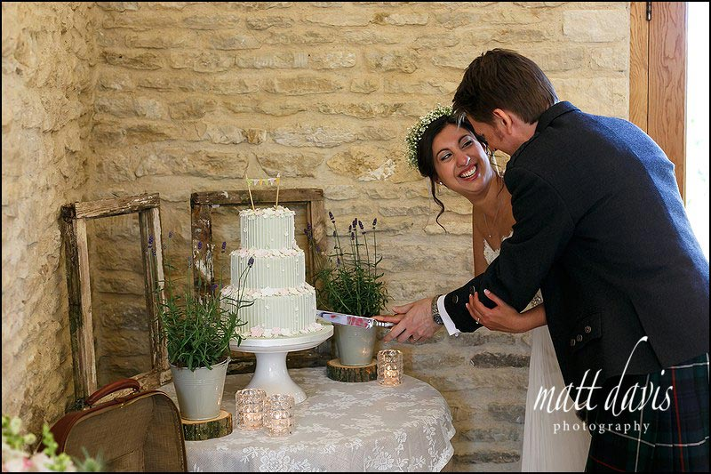Couple cutting wedding cake at Kingscote Barn