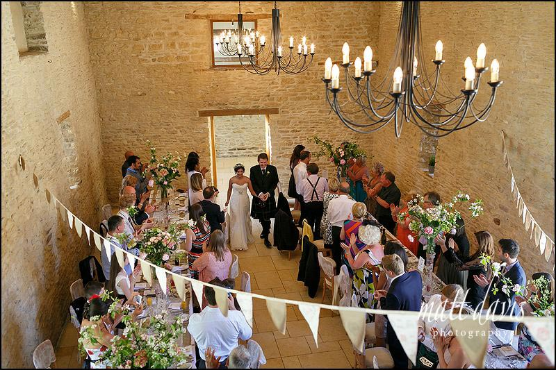 Wedding couple announced to the wedding breakfast after a beautiful outdoor wedding at Kingscote Barn