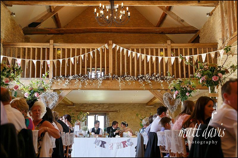 Guests sit to eat after a beautiful outdoor wedding at Kingscote Barn