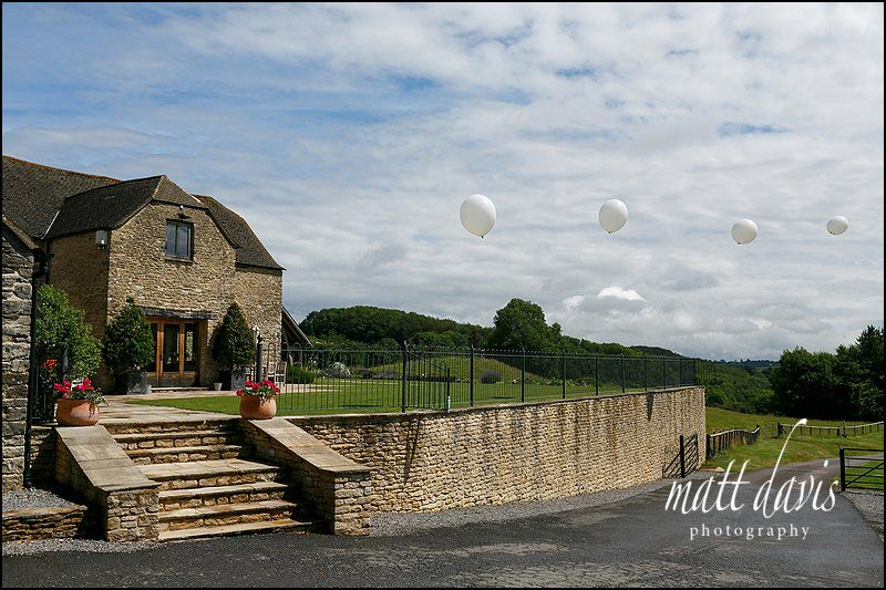 A summer wedding at Kingscote Barn with large helium balloons