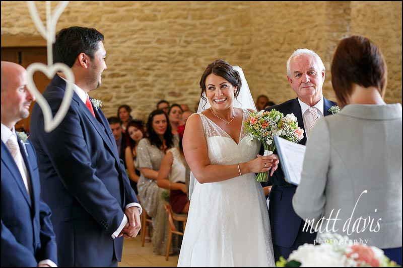 Bride and groom smiling during their wedding ceremony at Kingscote Barn